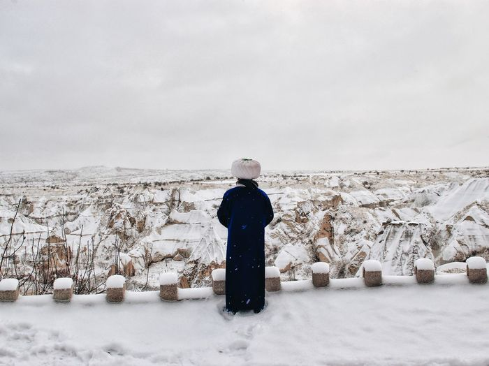 Rear view of man in traditional clothing standing on snowy field against sky