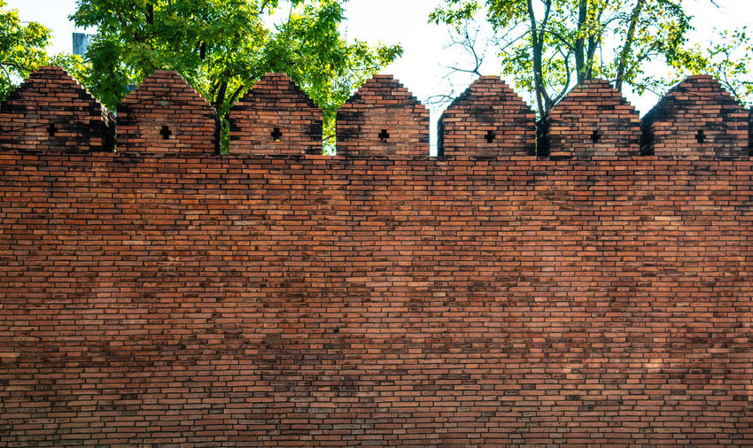 Low angle view of brick wall by building
