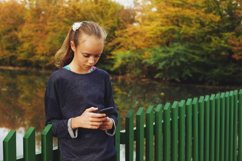 Girl using smarphone in a autumn park Child Beauty Children Only Nature Outdoors Looking Down One Girl Only Grass One Person Horizontal People Day Authentic Moments Real People Autumn Colors