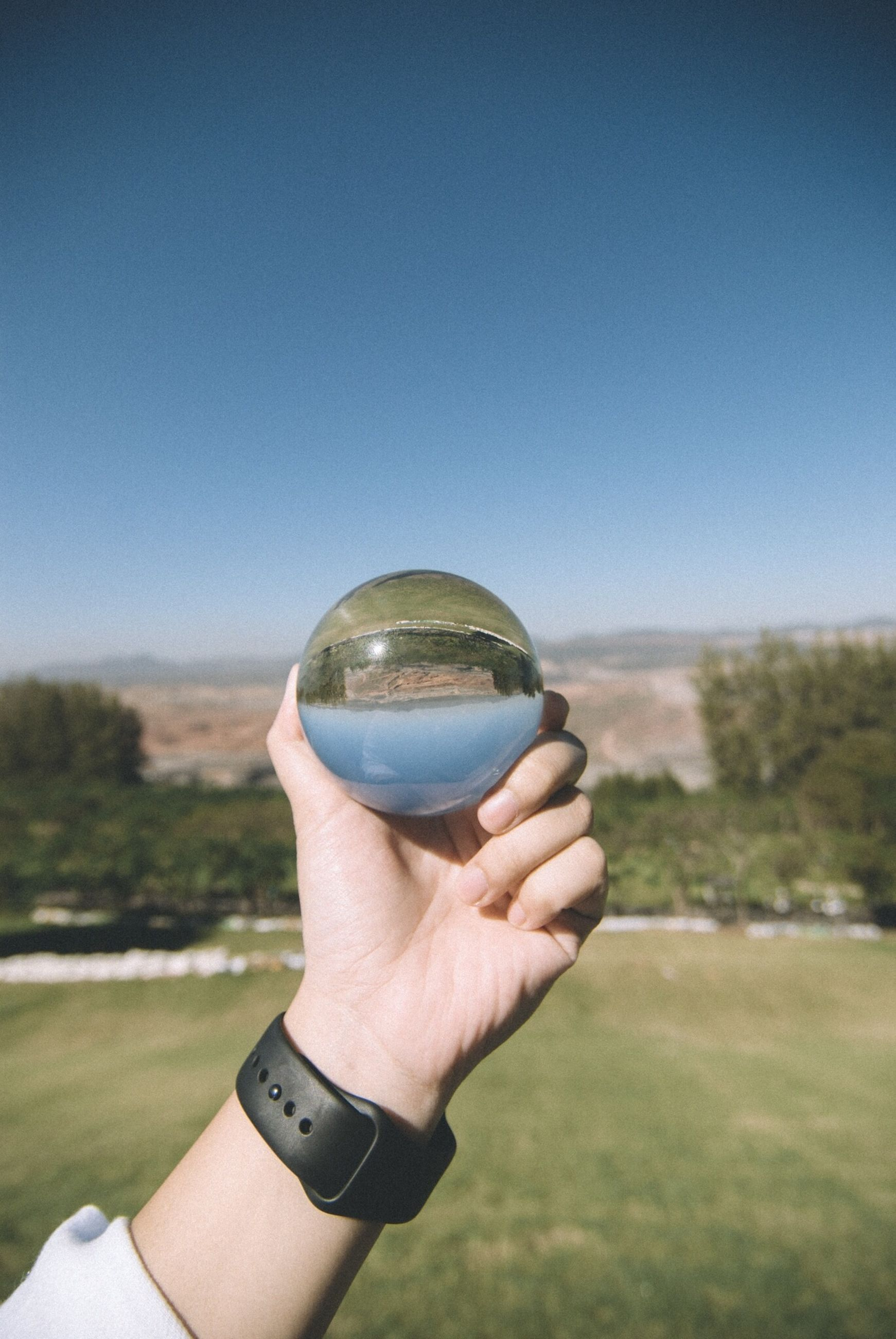 human hand, hand, human body part, holding, one person, sky, sphere, day, nature, clear sky, crystal ball, real people, blue, focus on foreground, personal perspective, transparent, glass - material, body part, landscape, outdoors, finger
