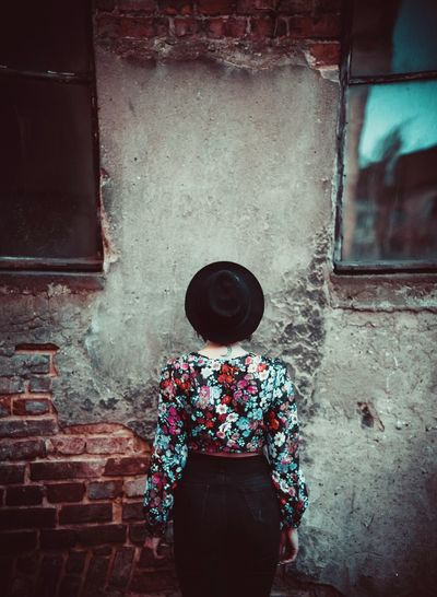 Rear View Of Woman Standing Against Old Wall