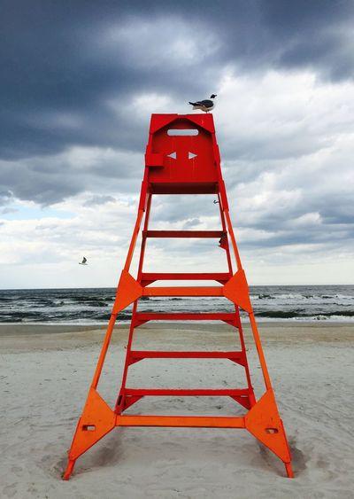 Bird perching on orange lifeguard chair at beach against cloudy sky