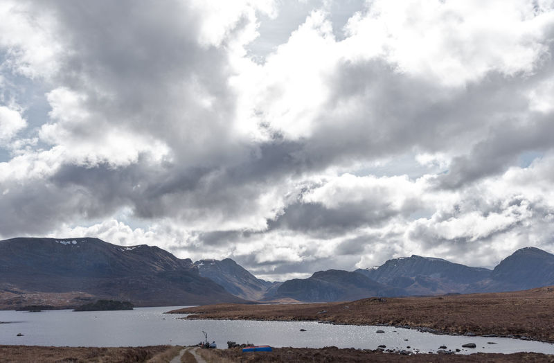 Upturned Small Boat On Shore Small Harbour Fionn Loch Walk Cloudy Scene Day Fresh Water Loch Mountain Range No People, Remote Places Tourist Destination Calm Tranquil Scene