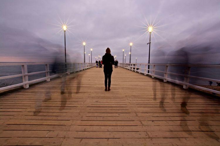 Rear view of man walking on illuminated bridge against sky