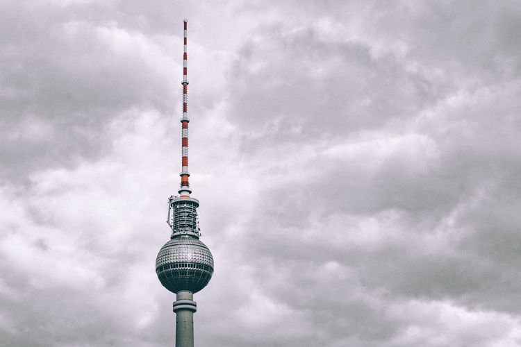 Television tower against cloudy sky