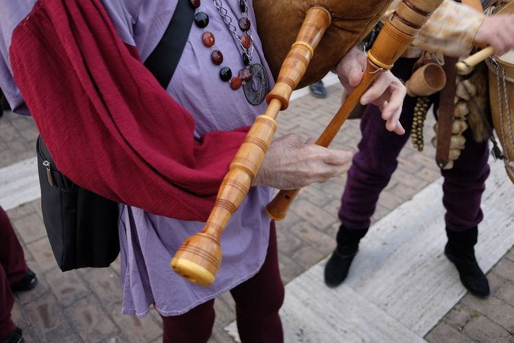 Midsection of male street artist playing bagpipe on footpath