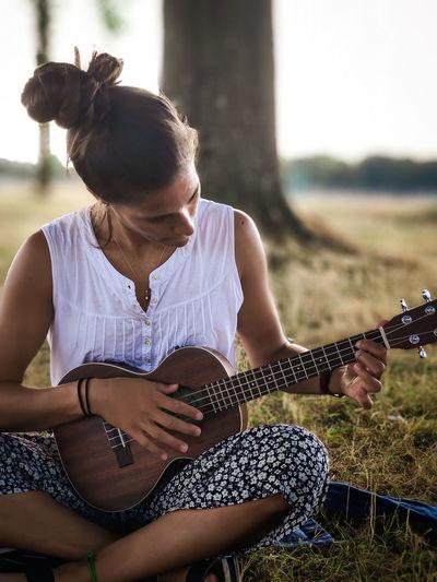 Woman playing ukulele while sitting on grass