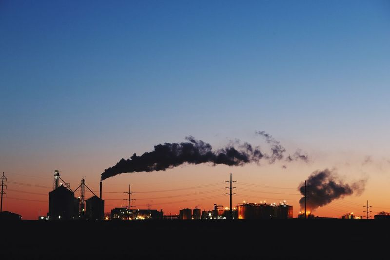Smoke emitting from factory against sky during sunset