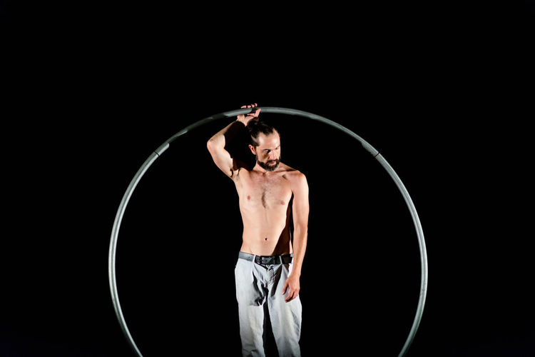 Circus Adult Arms Raised Black Background Clothing Front View Human Arm Indoors  Men Muscular Build One Person Performance Plastic Hoop Shape Shirtless Skill  Stage Standing Strength Studio Shot Three Quarter Length Young Adult