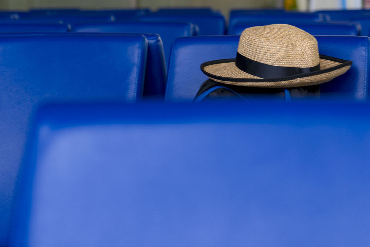 vacation is calling Straw Hat Traveling Holiday Moments Airport Departure Area Airport Terminal Airport Seat Selected Focus Royal Blue 🔷 Mode Of Transportation High Angle View Copy Space Table Absence Security Close-up Still Life