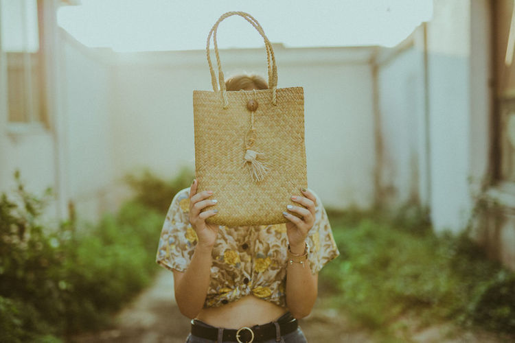 Woman holding wicker bag while standing outdoors