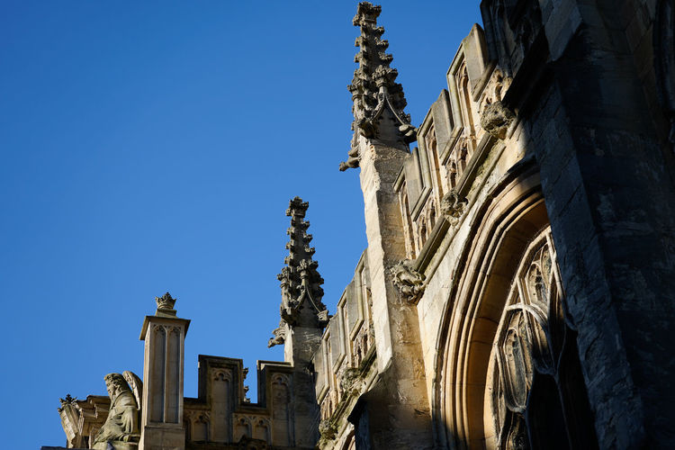 Low angle view of ornate on building against clear blue sky