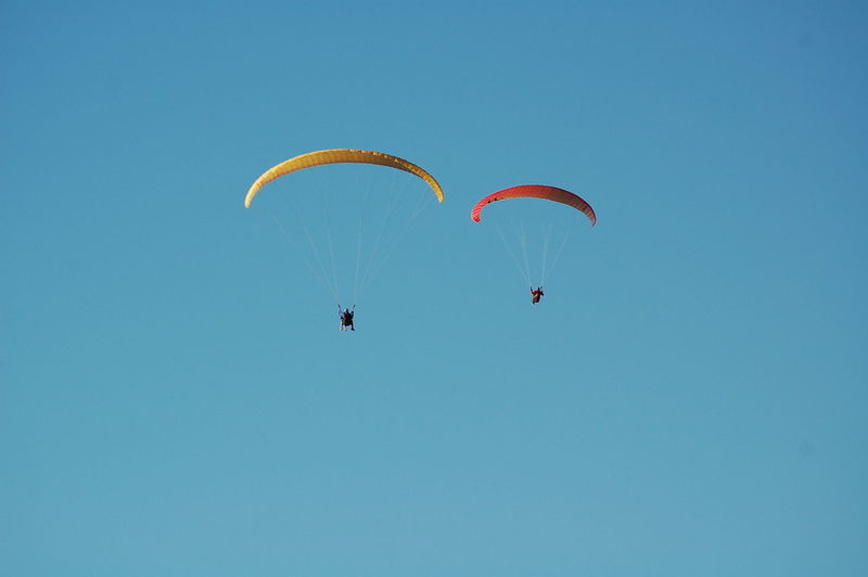 Low angle view of people paragliding against clear sky