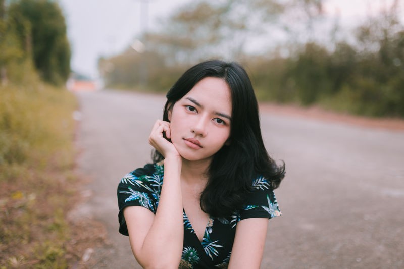 Portrait of beautiful woman with hand on chin at road