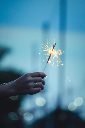 Close-up of hand holding sparkler against blurred background