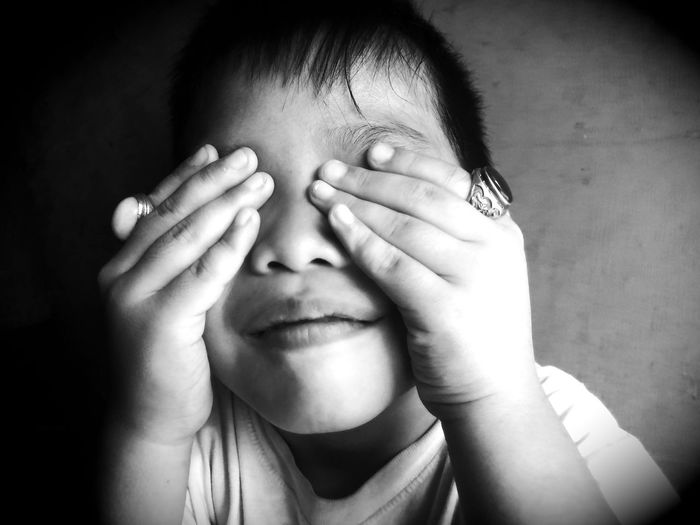 Close-Up Of Boy Covering Eyes With Hands