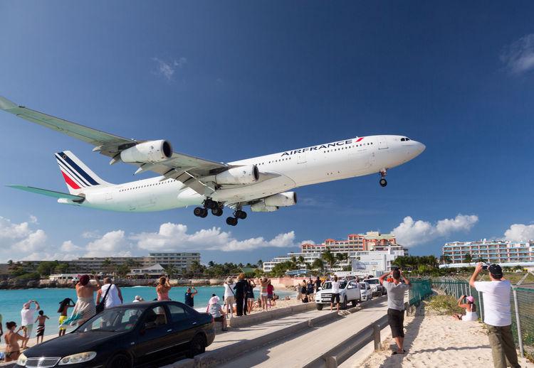 People on runway against sky