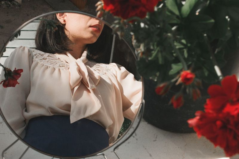 Young woman looking down while sitting on plant