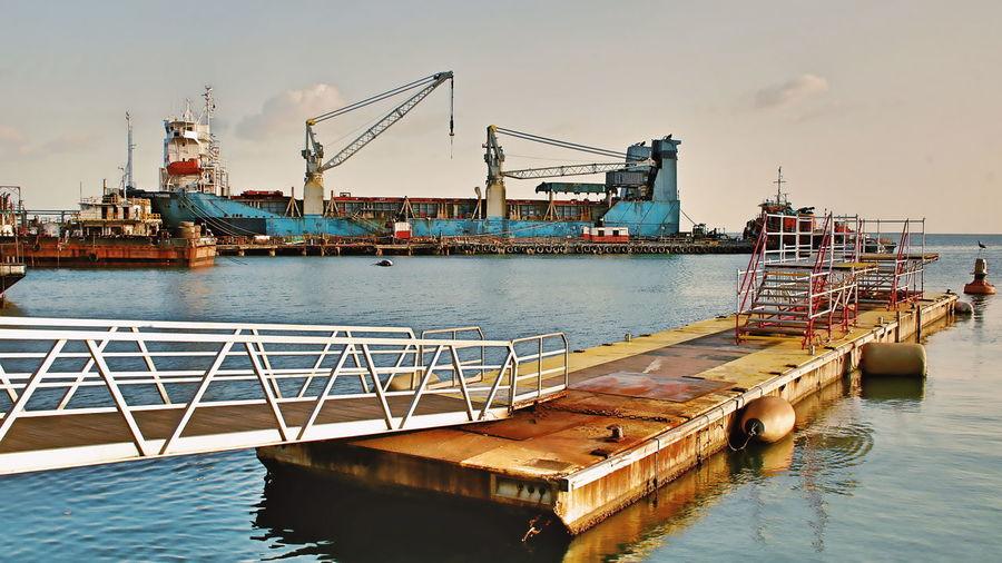 Cranes at pier against sky