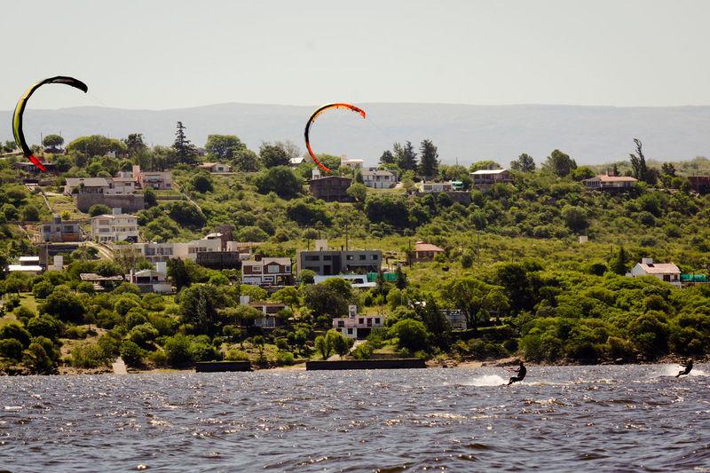 Kitesurfers against sky on sunny day