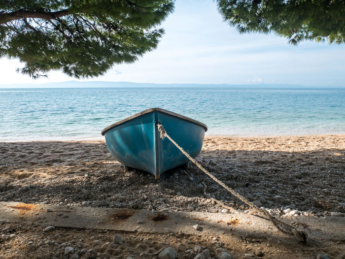 Small plastic boat on the beach under pine trees on sunny summer day Boat Sea Vessel Blue Water Nautical Vessel Sky Tranquility Beauty In Nature Nature Scenics - Nature Day No People Transportation Horizon Over Water Mode Of Transportation Outdoors Rowboat Small Beach Travel Tourism Summer Coast Coastline Nobody Empty Makarska Riviera Dalmatia Croatia Europe Adriatic Sea Mediterranean  Scenics Vacations Holiday Calm Pine Tree