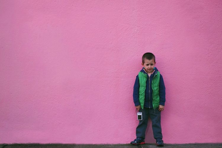 Portrait Of Boy Holding Camera While Standing Against Pink Wall