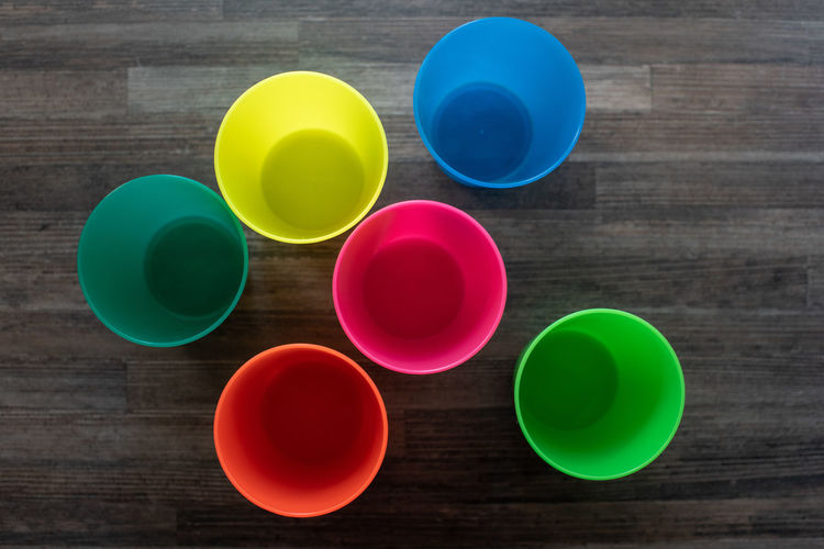 Cups Multi Colored Table Wood - Material Indoors  High Angle View Directly Above Variation Choice Green Color No People Still Life Group Of Objects Cup Close-up Geometric Shape Circle Shape Blue Drink Vibrant Color Plastic Cups