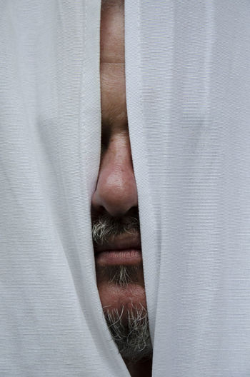 Close-up of bearded man behind curtain