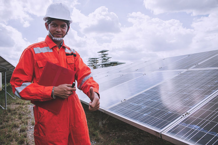 Portrait of worker wearing reflective clothing while standing on solar panel against sky