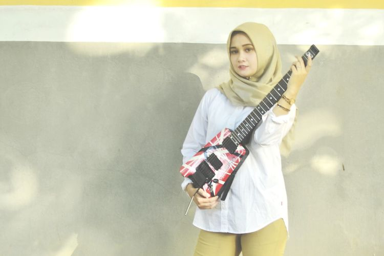 Portrait of teenage girl playing guitar against wall