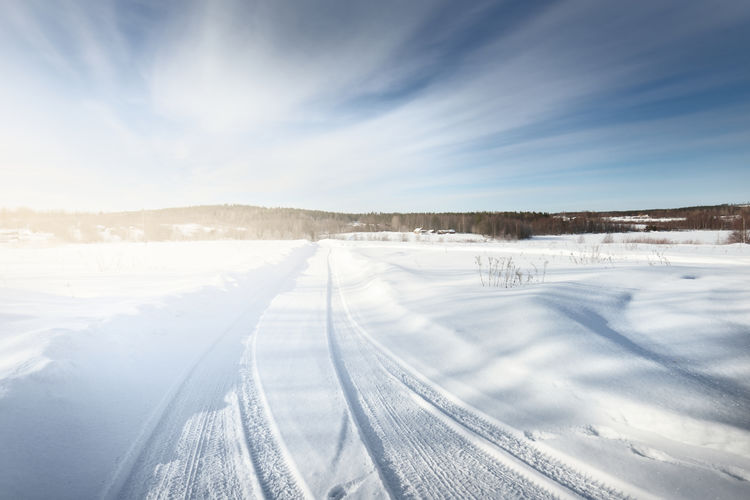 Scenic view of snow covered land against sky
