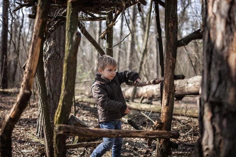 Boy standing by tree trunk