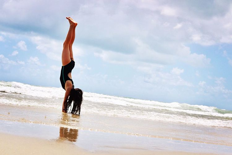 Young woman doing handstand on sea shore against cloudy sky