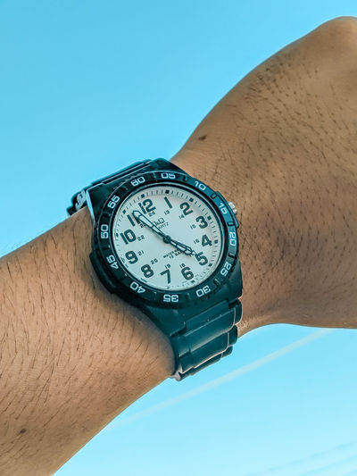 Low angle view of hand holding clock against blue sky