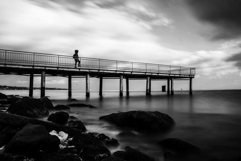 People standing on bridge over sea against sky