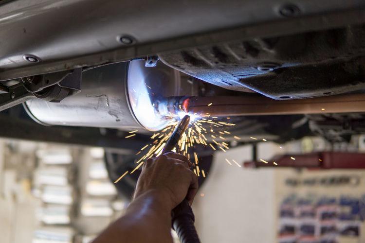 Cropped hand of mechanic repairing car in workshop
