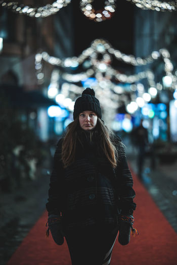 Portrait of woman standing in illuminated park during winter