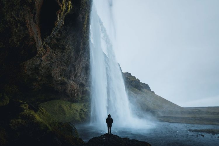 Rear view of person standing on rock by waterfall