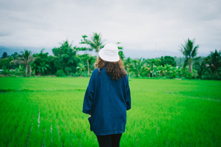 Casual Clothing Day Environment Field Grass Green Color Growth Hair Hairstyle Land Landscape Nature One Person Outdoors Plant Real People Rear View Rural Scene Sky Standing Three Quarter Length Tree Women