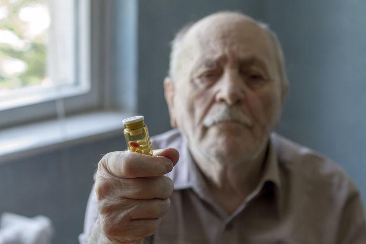 Portrait of man holding bottle of pills