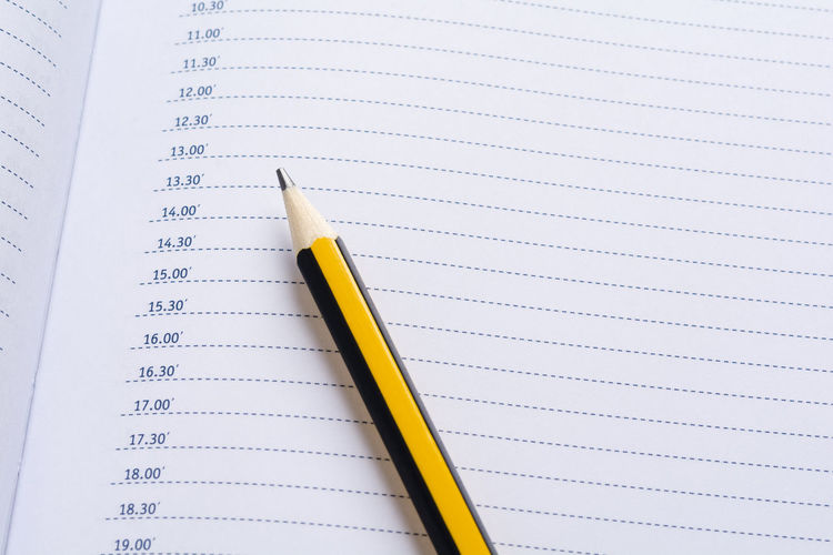 Pencil on a daily planner Appointment Business Daily Goals Office Organizer Organizing Plan Planning Schedule Working Write Analyzing Calendar Diary Memo Page Paper Pencil Personal Planner Reminder Text Time Yellow