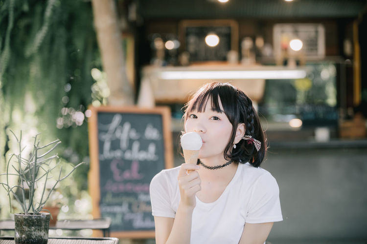 Portrait Of Young Woman Eating Ice Cream At Restaurant