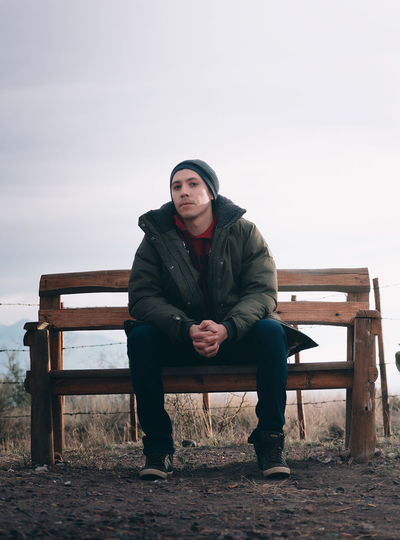 Portrait of man sitting on bench against sky