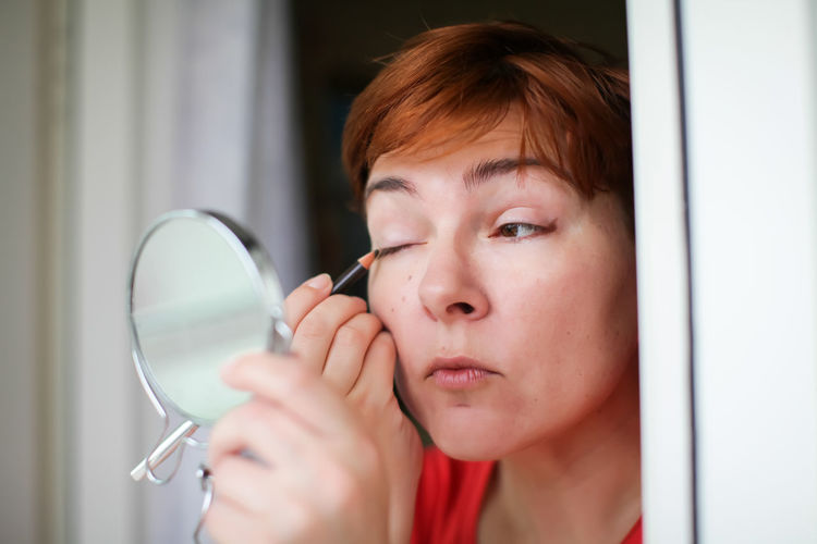Close-Up Of Woman Applying Eyeliner With Mirror At Home