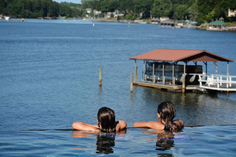 Rear view of sisters swimming in infinity pool by lake norman