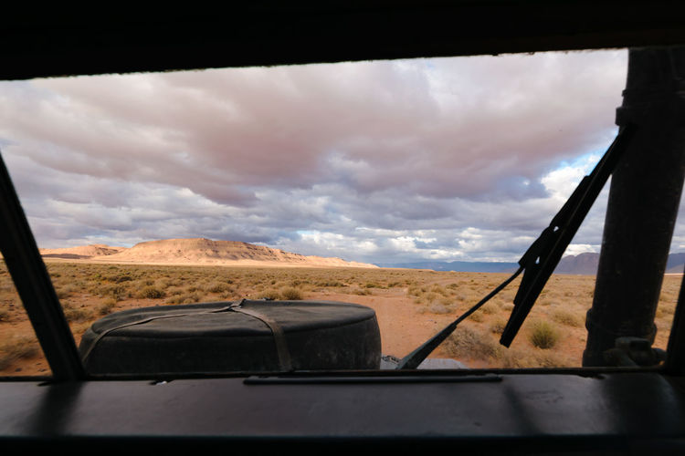 View from the drivers position of an four by four oldtimer off-road vehicle driving off- road in a stone desert in Morocco. You can see the spare wheel on the hood. 4x4 Adventure Africa Automotive Cockpit Cockpitview Day Desert Drive Expedition Explorer Morocco Nature No People Off-Road Oldtimer Outdoors Overland Road Safari Sky SUV Truck Vehicle Windshield