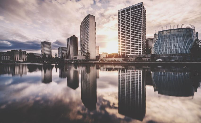 Reflection of buildings in city against cloudy sky during sunset