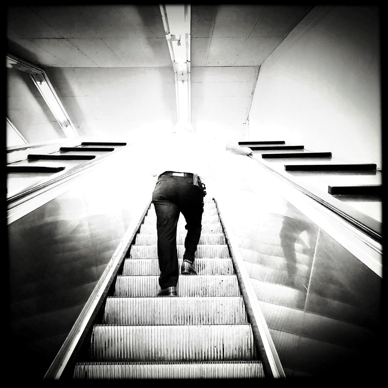 architecture, staircase, steps and staircases, one person, railing, real people, full length, indoors, built structure, lifestyles, escalator, the way forward, direction, rear view, auto post production filter, moving up, transportation, men, transfer print, modern, moving walkway