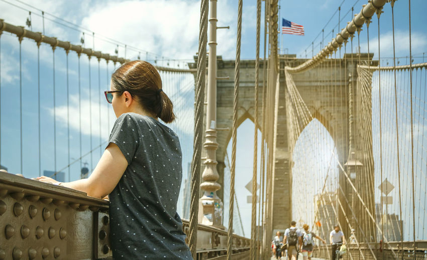 Young woman standing on bridge against sky