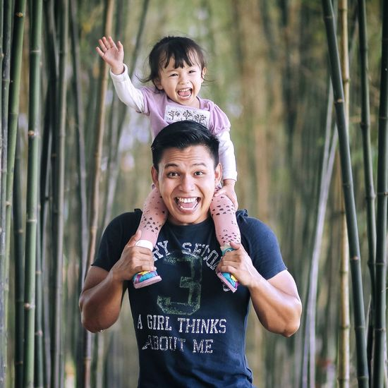 Portrait Of Cheerful Father Carrying Daughter On Shoulders In Forest